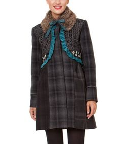 Fusing together a mix of captivating graphics that exude chic edge, this long jacket effortlessly maximizes a minimal palette with a handful of style through faux fur collar and teal ruffle trim.
