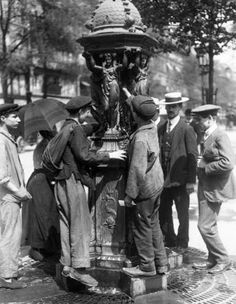 People drinking from a Wallace fountain during Bastille Day celebrations in 1911
