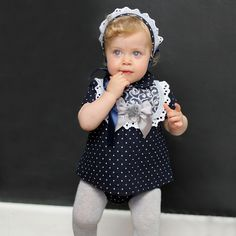 Baby girls navy blue dress, bloomers and bonnet 3 piece set by Foque, covered with white polka dots. The pretty, lined dress has a blue jacquard 'bib' trimmed with blue embroidery and edged in lace. It has a central, grey grosgrain bow with synthetic fur and a mother-of-pearl logo charm, with a button fastener at the back. Comes with a matching, cotton-lined bonnet, tied with a navy blue ribbon and knickers with an elasticated waist and cuffs