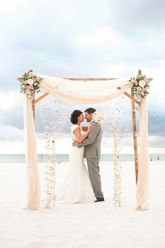 Bride and Groom Clearwater Beach Wedding Ceremony with Bamboo Alter and Pastel Pink Flowers and Hanging Seashells