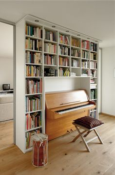 bookshelf wall around the piano except our piano is taller and our wall is shorter, and longer.