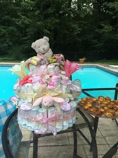 Girl Diaper Cake  -Used 32 pack of Newborn Diapers and 24 pack of 6 months - Ribbon - Cute baby toys, Bottles and Rattles as decoration that tie in with the theme.  - 16' in. Cardboard Cake dish as base.  - Roll diapers and put a rubber band around them to keep together.