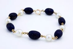 The bracelet is made out of beautiful 14k Yellow Gold and feature gorgeous carved Lapis Lazuli gem stones and cultured pearls! One of the Lapis gem stones is slightly chipped near the top.