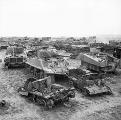 The remains of Sherman tanks and carriers waiting to be broken up at a vehicle dump in Normandy, 1 August 1944. All salvageable parts have been removed and the remaining components are shipped back to Britain to be smelted down and used in the production of new vehicles.
