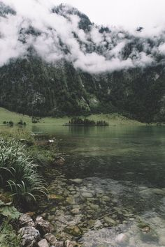 Lake with green waters by a cliff in the clouds