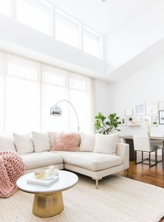Dreamy space // bright feminine living room with white sectional and gold and white coffee table
