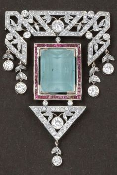 An Art Deco gold, diamond, aquamarine and ruby brooch. Centring a rectangular aquamarine framed by calibré rubies, surmounted by stylised geometric foliate and swag set with brilliant-cut diamonds, suspending a triangular pendant with foliate motif set with brilliant-cut diamonds. #ArtDeco #brooch