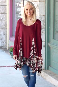 OMG! Staff favorite! Long sleeve knit tunic top with a rose floral print spliced out of it and ruffled trim! So cute and so flattering! Burgundy in color with the rose print being a wine, blush, cream