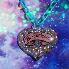 Handmade resin necklace says Bi-Furious across a hand-drawn scroll on a background of holographic silver glitter.  This necklace is made to order,
