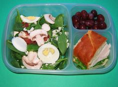 Delicious spinach salad with egg and bacon. Served with a small turkey sandwich and grapes.