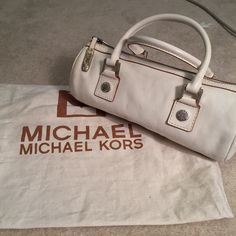 Vintage Michael Kors Ivory Leather Cylinder w Dust Real Fabulous 1981 or later Michael Kors ivory leather cylinder vintage handbag with 2004 dust bag. Zippered top. Interior zippered pocket. Interior small leathered strap with clip. Cloth Michael Kors dust bag with Michael Kors on it. Condition: pre-loved, interior good - no ink, exterior good- small mark here and there, some patina on Handel and zipper hardware. Overall good condition for being vintage. Michael Kors Bags Satchels