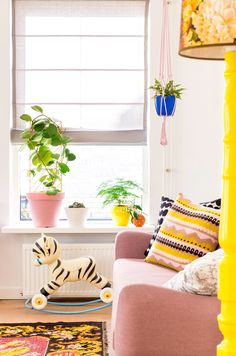 bright and fun play room with colorful indoor plant pots, rocking tiger, and pink couch with embroidered pillows