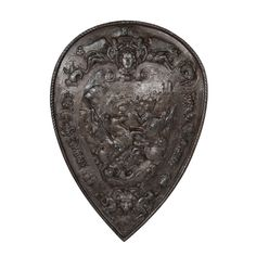 Antique Iron Decorative Shield. This beautifully cast antique iron decorative shield is a reinterpretation of a 16th century shield made for King Henry II of France, which is now housed at the Metropolitan Museum of Art. This decorative shield was likely cast in France. It seems to have hung very near a fireplace as the back has a layer of soot. The front has a silver finish, which highlights the fine details.