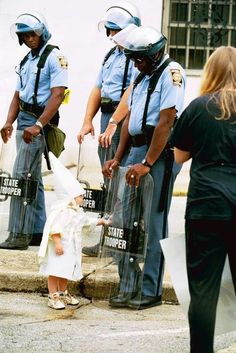 A small white boy touches the riot shield of a black state trooper at a Ku Klux Klan rally in Atlanta, Georgia, 1992.