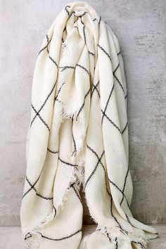 """We can draw up one thousand and one outfits for you in the Graph Theory Cream Grid Print Scarf! Soft woven fabric (with tasseled trim) has a black and light beige grid print. Scarf measures 60"""" wide, 60"""" long."""