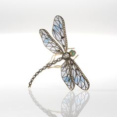 An Art Nouveau chalcedony, diamond and enamel dragonfly brooch, featuring blue and lavender plique-à-jour enamel wings edged in old mine and single-cut diamonds.   Circa: 1900