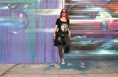 Lisa Marie of La Ruta Sin Fin with a colorful street art graffiti in the funky Downtown Arts District of Los Angeles, California.