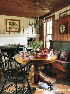 Quaint dining area with low wood-paneled ceiling, fireplace, rustic bench, and black Windsor chairs.