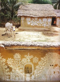 India - Sacred Cow in front of a hand painted village cottage