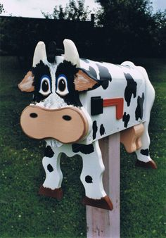Cute Cow mailbox - Mailboxes are USPO approved. The mailboxes are handcrafted and hand painted. This mailbox was made by the talented artist Michel Devost in Quebec, Canada. You can even send Michel a photo of your pet, and he will make you a mailbox that is as much as possible a replica of your pet! For more information and orders contact Michel at: http://pages.globetrotter.net/miche/mailboxes.html