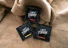 Nuovo pack per le cialde Caffè Torre in total black: logo più grande e fascia colorata che rappresenta le diverse miscele. Packaging by Agenzia AT&ACME