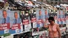A woman walks past pre-election posters in Athens on June 16, 2012. (PASCAL ROSSIGNOL/REUTERS)