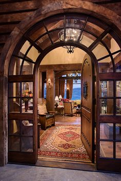 Arched glass surrounding wood front door.  Locati Architects and Interiors.  Mountain ski lodge. Yellowstone Club, Montana.