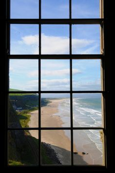 Viewing de beach of Downhill Demense n Benone Atlantic Ocean wif de Belfast/L'Derry railway line below. De hills of Donegal r in de distance, thru de window inside de Mussenden Temple of Ireland