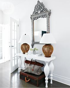 white console, ornate mirror, woven lamps