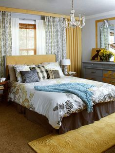 Apartment Decorating Ideas: A wall of drapery adds elegance to a room. And it's not permanent. Hang several sets of drapes behind your bed to give it style and personality. It's also a great way to balance out a wall with an oddly placed or sized window.
