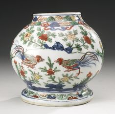 A WUCAI WALL VASE  MING DYNASTY, WANLI PERIOD of globular form supported on a splayed foot with a flat back, painted in underglaze-blue, iron-red, green and yellow enamels with a pair of confronted cockerels amongst prunus and peony sprays issuing from pierced rockwork, with birds in flight above amongst stylized clouds, between ruyi-head bands around the neck and a foliate scroll band around the base