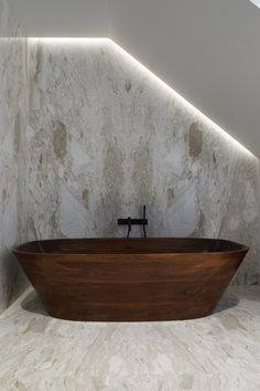 Biggest Indulgence: The solid mahogany soaking tub by designer Nina Mair. The form is so modern it's hard to believe it can be fabricated with wood.