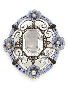 A Victorian rock crystal, enamel, seed pearl and rose-cut diamond brooch, circa 1880. The step-cut rock crystal within a scrolling openwork surround of blue, black and white enamel set flowerheads at the cardinal points with seed pearl buds, and highlighted with rose-cut diamonds. #Victorian #brooch