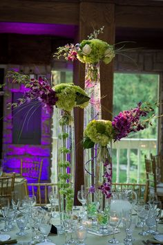 purple and green flowers feel slightly tropical but also modern in these tall arrangements