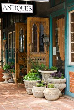 A grouping of similar container pots decorate  a store front in downtown Fredericksburg, Texas.