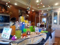 Colored water, homemade slime and scientific looking glassware create a Mad Scientist themed birthday party.
