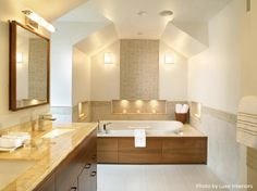 Mosaic tile accent wall, tile wainscot and a large soaking tub in a contemporary styled bathroom.