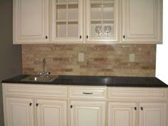 Lowes Caspian Cabinet, grey marble countertop, stone tile backsplash.