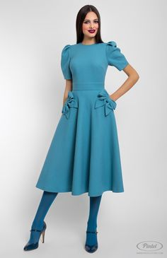 Slim-fit genuine wool dress. Round neck. Short tucked sleeves. Side pockets decorated with fixed designer handmade bows. Hidden back zip closure.