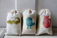 carved out 3 animal shapes and block print them onto little cotton drawstring bags.