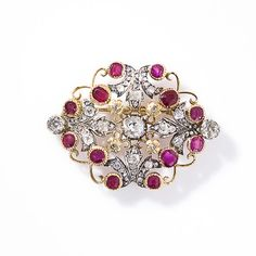 This rare and resplendent nineteenth-century brooch is crafted in silver over gold and glistens with twelve deep red Burmese rubies, three old mine-cut diamonds and and four diamond studded fleur d'leis which point to the center diamond. Four diamond set flowers in between the fleur de lys complete the picture of this outstanding and opulent high Victorian treasure. 1 7/8 inches inches across by 1 3/8 inches tall.  Victorian