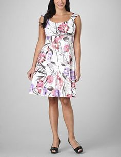 Slip into this sleeveless sateen dress and instantly transform into a princess! It is extra girly with its slightly fitted body that flares into a fuller skirt. Allover floral print is bold and colorful and has a tropical feel. Scoop neckline with a slightly ruched bodice and piped empire waist creates an ultra-flattering fit. Back zip. fashionbug.com