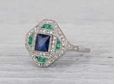Antique Edwardian ring made in platinum and centered with an approximately 1.12 carat sapphire and accented with emeralds. Circa 1925. A bold and graphic ring with classic Deco flare. Diamond and gold