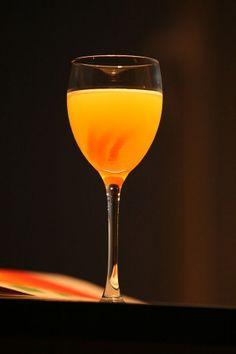 The Orange Blossom Cocktail in the goblet garnished with orange peel spiral (Коктейль Цветок Апельсина в винном бокале украшенный спиралью из кожуры апельсина)