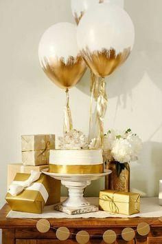 Decoração de chá de bebê dourado e branco