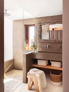 Baño en microcemento marrón, con ducha con murete y cristal y plato de piedras, lavamanos de obra, balda y espejo rústico 00436710
