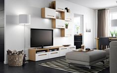 A living room with a TV bench in oak with white drawers and wall cabinets with white doors. Shown together with a light grey footstool with chrome-plated legs.