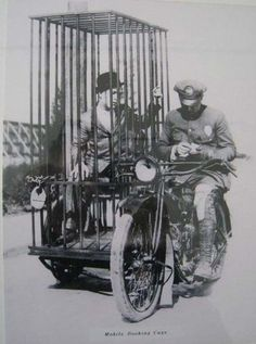 7.) A police officer on a Harley-Davidson transports a prisoner in a holding cell (1921).