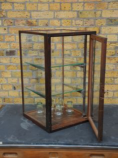 Antique display cabinet removed from a tool shop. Heavy duty but delicate oak frame with original glass and brass fittings - including an ingenious handle. Original condition.  created by: Barrett of Camberwell  origin: UK  year: 1920