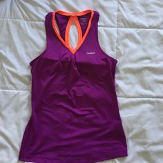 """Purple """"reebok"""" workout tank size small NWOT. Purple workout tank with built in bra and key hold back. Has bright orange accents. Selling for $12 or will bundle with the reebok shoes for $8. Reebok Tops Tank Tops"""